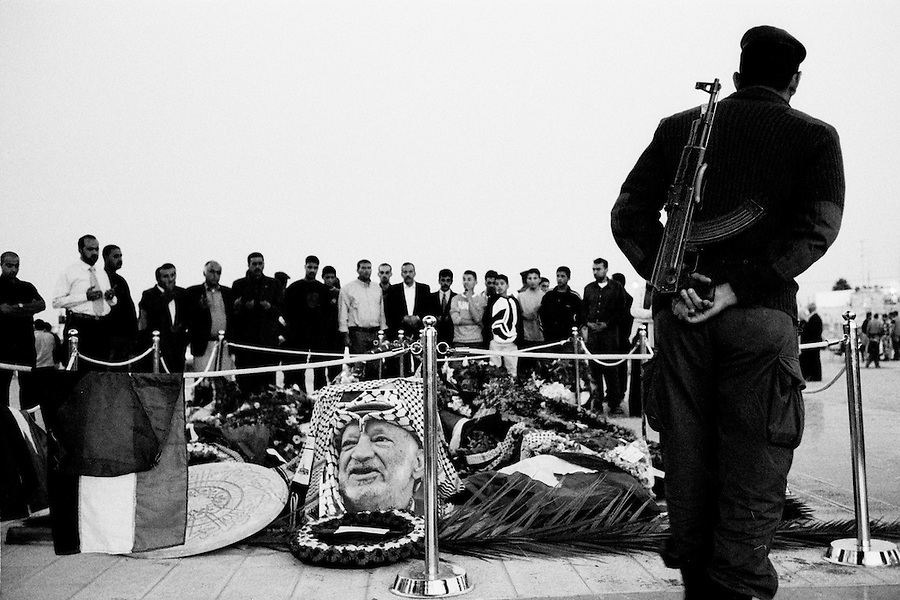 Guard watching over mourners at Yasser Arafat's burial site.