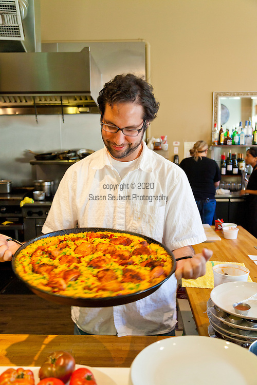 Proprietor David Rosales holding the signature Paella in the open kitchen of Andaluz, a Spanish Tapas restaurant in downtown Salem, Oregon