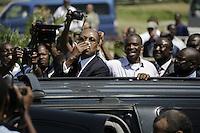 HAI02- PUERTO PRÍNCIPE (HAITÍ), 18/03/2011.- El ex presidente haitiano Jean Bertrand Aristide saluda a sus seguidores al subirse a su vehículo en el aeropuerto Internacional Toussaint Louverture hoy, viernes 18 de marzo de 2011, antes de dirigirse a su casa de Puerto Príncipe, donde varios miles de personas se congregaron para darle la bienvenida a su regreso desde Sudáfrica, donde pasó siete años exiliado tras el golpe de Estado de 2004. EFE/Andrés Martínez Casares..