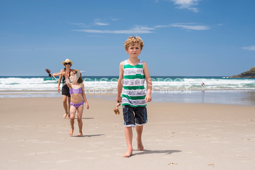 Family (mother and two children) walking back up golden sand beach from the sea on a summers day, Whangarei Heads Northland, New Zealand - stock photo, canvas, fine art print