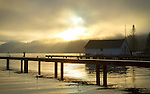 Washington, Western, Bellingham. Sun burns through morning fog over Whatcom Lake with a dock and lakeshore boathouse.