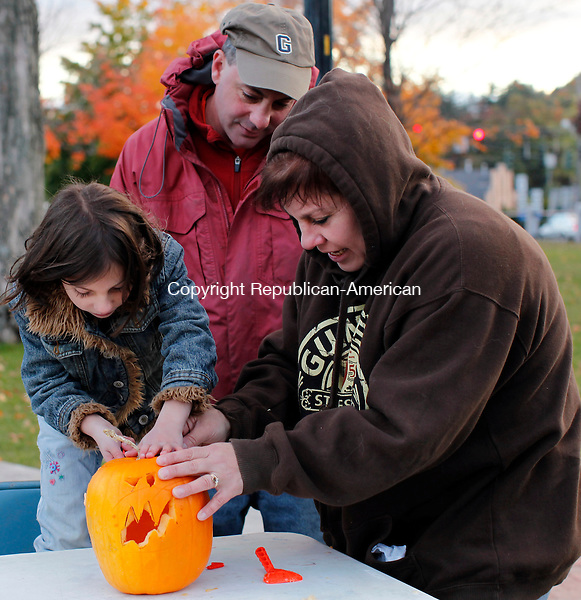 Winchester CT- 22, October 2010-102210CM01  Chelsea Gillotte, 8, carves a pumpkin with her parents, Sheri and Darryl, from Winchester, Friday night at East End Park in Winsted.  The pumpkins were then lit and put on display. The event was put on by Tricia Twomey and the Town of Winchester Recreation Department.  Christopher Massa Republican-American