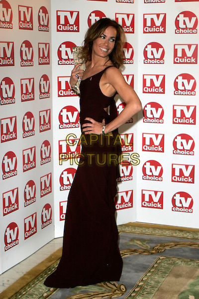 TARA PALMER TOMKINSON.Inside Arrivals at the TV Quick & TV Choice Awards, The Dorchester Hotel, London, England. .September 3rd 2007.full length brown dress off the shoulder silver metallic clutch purse bracelet looking over shoulder hand hip .CAP/AH.©Adam Houghton/Capital Pictures