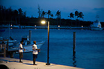 Two young boys fishing at dusk on dock at Cape Eleuthera, Bahamas