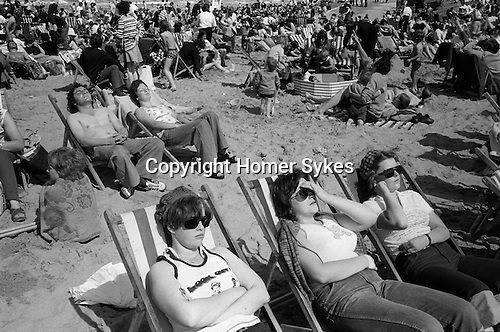 Blackpool Beach, Lancashire Uk. 1970s. Holidaymakers sun themselves, crowded beach. ..