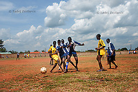 Members of Girls Kick It (in blue) play soccer during a tournament at Pece Stadium, Gulu District. Many of the Girls Kick It players were abducted by Lord's Resistance Army (LRA) and soccer is a way of reintegrating them back into community.