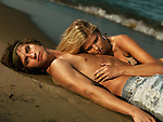 Young woman in bikini and a young man in jeans lying on the shore