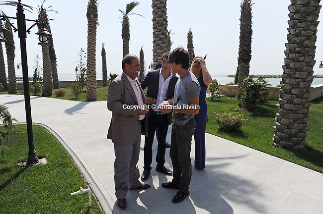 (L-r) Ibrahim Ibrahimov, an Azerbaijani oligarch and billionaire, passes money to his sons Huseyn, 18, and Hasan, 16, as his wife Valida Ibrahimli looks on outside one of several houses on his Caspian seaside property he used to inhabit with his family in the Garadagh region just southwest of Baku, Azerbaijan on July 18, 2012.  Ibrahimov is the developer behind the Khazar Islands artificial islands project; in his private life, he enjoys building a home for his family, moving in, and then quickly tires of the property before building a new home on an adjacent lot on his seaside lands.