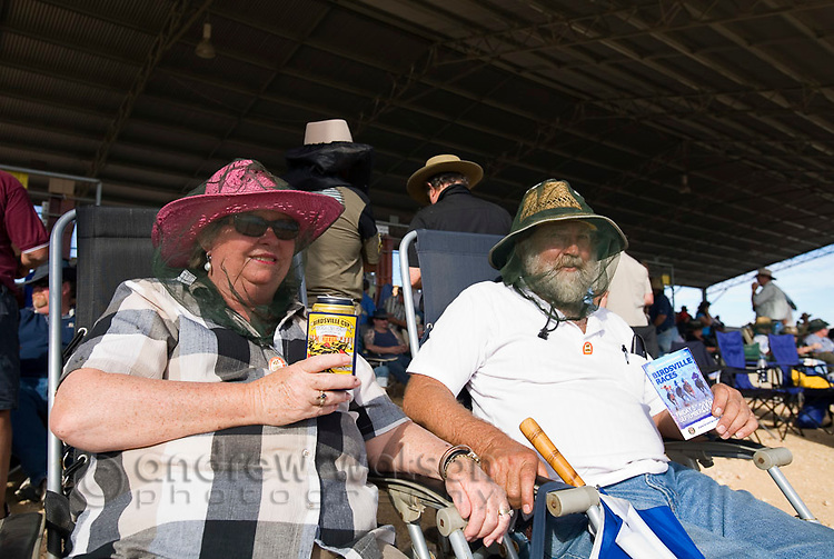 Race goers wearing fly nets at the annual Birdsville horse races.  Every September the small outback town of Birdsville hosts thousands of visitors for the Birdsville Cup, one of the most famous racing carnivals in Australia.  Birdsville, Queensland, AUSTRALIA.