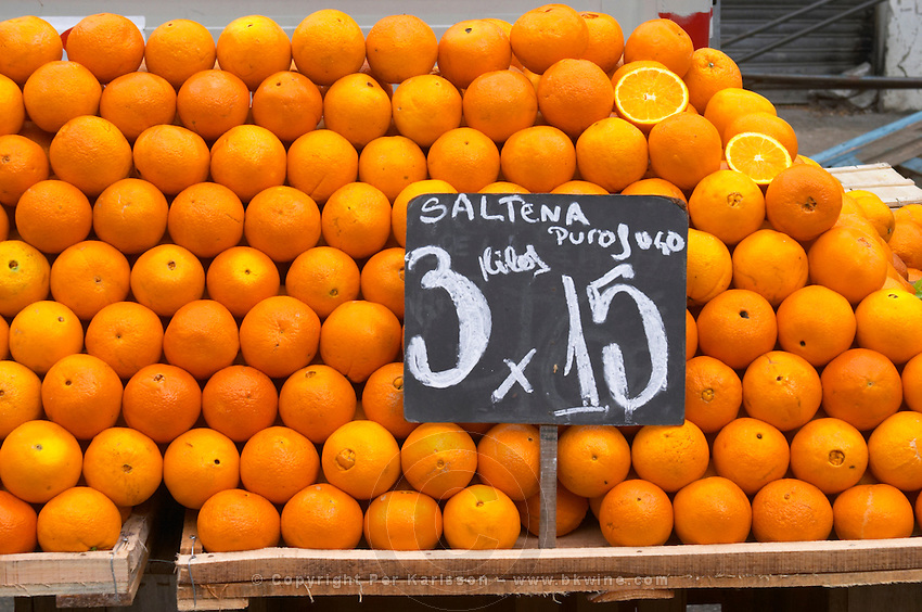 A market stall street market merchant selling oranges in big piles, Saltena Puro Jugo Montevideo, Uruguay, South America
