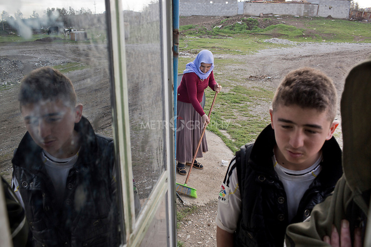 17/02/15 --TANJERO, IRAQ: Ghazal sweeps outside the shipping container where she lives while Sardesht looks into the cabin where his brothers and cousin sleep.<br /> <br /> The family of Yezidis, displaced from Sinjar, live next to an oil refinery in the Kurdish Region of Iraq. The young men run the refinery 24 hours a day with little to no safety equipment. Reporting for this article was supported by a grant from the Pulitzer Center on Crisis Reporting