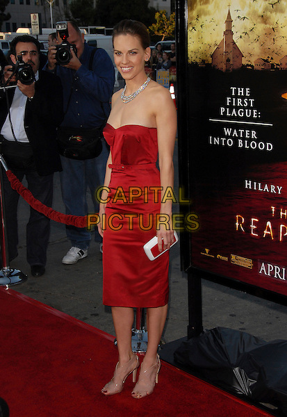 "HILARY SWANK .The Warner Brothers' Pictures L.A. Premiere of ""The Reaping"" held at The Mann Village Theatre in Westwood, California, USA..March 29th, 2007.full length red strapless dress belt diamond necklace white clutch purse .CAP/DVS.©Debbie VanStory/Capital Pictures"