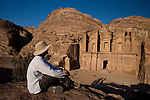 A male tourist in a hat visits the Al-Deir, or Monastery, one of the most magnificent sights in the Nabatean ancient city of Petra, Jordan.