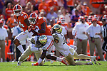 Travis Etienne (9) of the Clemson Tigers is tackled by Cameron Glenn (2) and Jessie Bates III (3) of the Wake Forest Demon Deacons during first half action at Memorial Stadium on October 7, 2017 in Clemson, South Carolina. The Tigers defeated the Demon Deacons 28-14.  (Brian Westerholt/Sports On Film)