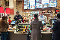 Burger lovers order at the new Smashburger restaurant in the shadow of the Empire State Building in New York on its grand opening day, Thursday, April 10, 2014. The popular Colorado chain, which has a cultish following, opened its first Manhattan outpost  bringing their burgers, smashed to order to the Big Apple. The fast casual restaurant has a loyal fan base and has 260 restaurants worldwide. The franchise welcomed their Manhattan customers by offering a free Classic Smashburger to each patron all day, with the line eventually stretching around the block.  (© Richard B. Levine)