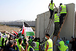 "Local and international peace activists pull down a concrete block, part of Israel's controversial separation barrier, during a protest in the Qalandia refugee camp, near the West Bank city of Ramallah, on November 9, 2009 to mark the 20th anniversary of the fall of the Berlin Wall in Germany. Palestinians are using the anniversary of the end of the Berlin wall to press their campaign against Israel's ""wall"", mostly a razor-wire fence interspersed with concrete barricades which Israel began building around the West Bank in 2002. The Jewish state has come under international censure for the barrier's de facto annexation of occupied West Bank land.. Photo by Issam Rimawi"