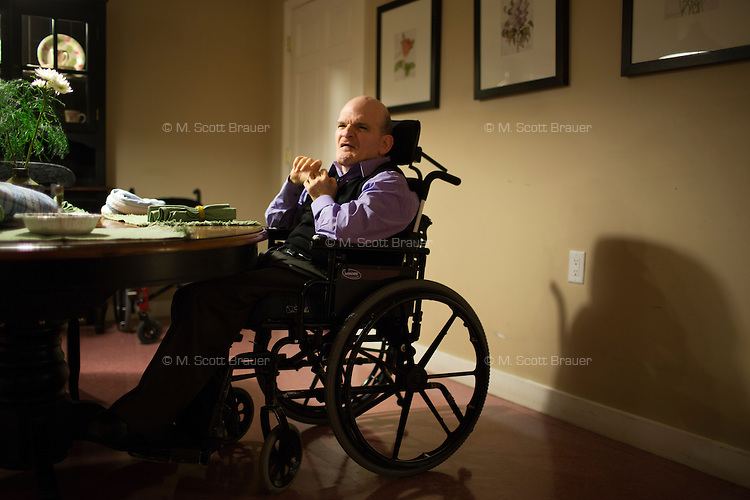 Frank Bandolfh, 56, (left) sits at a table for dinner as Kevin Calahane, LPN, feeds resident David Gilmore, 66, (right), at an assisted living home run by Northeast Residential Services in Bedford, Massachusetts, USA.  The residents previously lived at the Fernald Developmental Center in Waltham, Massachusetts, USA.