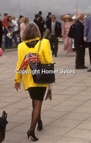 The Derby Horse race Epsom Downs Surrey Uk Circa 1985. Stylish woman carrying a Union Jack flag.