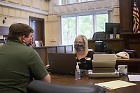 Donna Jones, financial administrator, (center) closes a purchase for Jay Wilson of Bella Vista (left), Friday, June 26, 2020 during a property auction at the Benton County Courthouse in Bentonville. The Benton County Circuit Clerk offered 25 Bella Vista properties at a judicial sale. The Bella Vista Property Owners Association requested a commissioner to sell foreclosures that were delinquent on payments. Other properties resulted from divorce sales. All of the properties sold to individuals. The next judicial sale is scheduled for September 4th. Check out nwaonline.com/200627Daily/ for today's photo gallery. <br /> (NWA Democrat-Gazette/Charlie Kaijo)