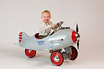 Children posed in a toy airplane on a white background.