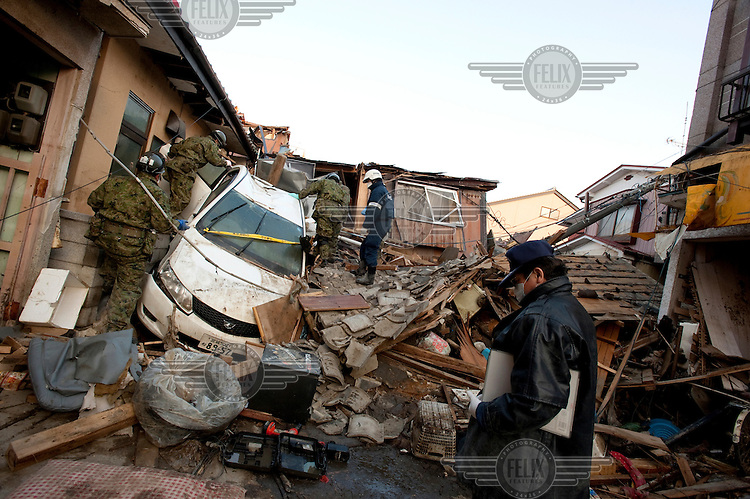 Emergency relief personnel and Japan Self Defence Forces (JSDF) soldiers searching through wreckage of houses in Kesennuma, a town in Miyagi prefecture that was almost totally destroyed by the earthquake and Tsunami.  On 11 March 2011 a magnitude 9 earthquake struck 130 km off the coast of Northern Japan causing a massive Tsunami that swept across the coast of Northern Honshu. The earthquake and tsunami caused extensive damage and loss of life.