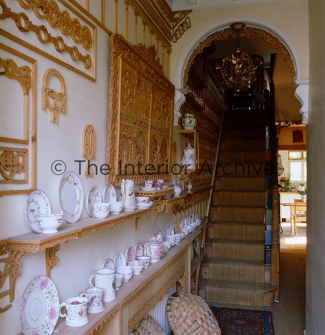 A collection of porcelain is displayed on the fretwork shelves which line this entrance hall