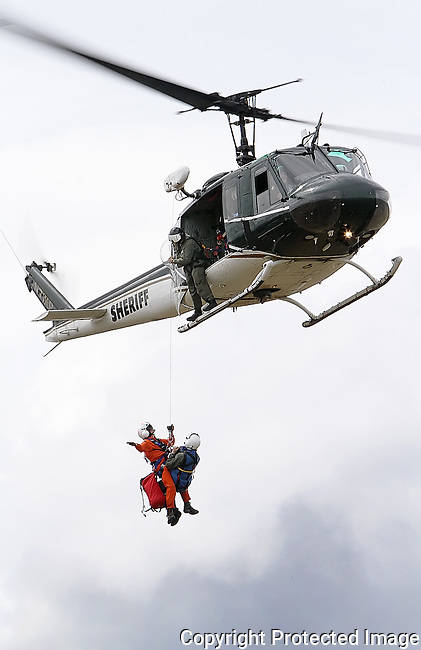 Members of the King County Sheriff's Office aviation unit perform a hoisting demonstration with their Bell UH-1 helicopter during interagency training exercises near Rotary Park in Ellensburg, Wednesday, June 26, 2013. (Brian Myrick / Daily Record)