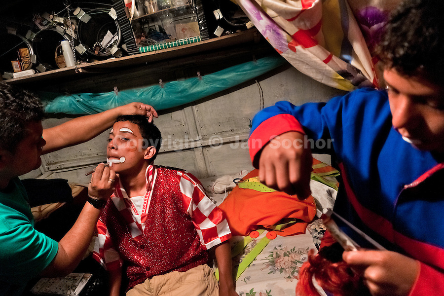 A Colombian boy has a color applied to his face to set his clown makeup before a performance at the Circo Anny, a family run circus wandering the Amazon region of Ecuador, 4 July 2010. The Circo Anny circus belongs to the old-fashioned traveling circuses with a usual mixture of acrobat, clown and comic acts. Due to the general loss of popularity caused by modern forms of entertainment such as movies, TV shows or internet, these small family enterprises balance on the edge of survival. Circuses were pushed away and now they have to set up their shows in more remote villages. The circus art and culture is slowly dying.