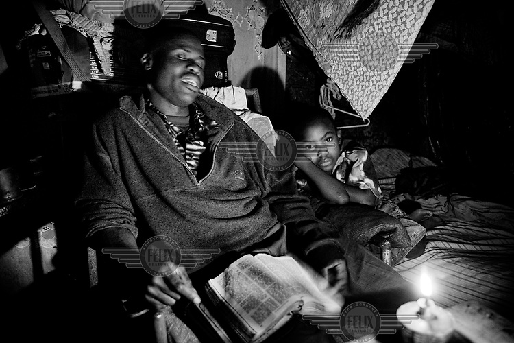 Augustin Odongo reads the bible with his daughter Cynthia. Every evening before going to bed in their home in Kibera, the whole family prays.