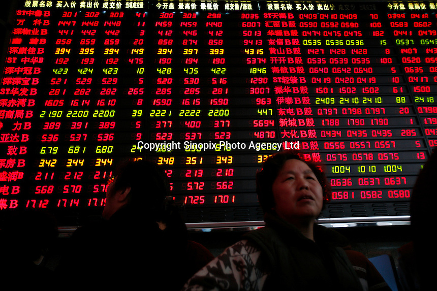 Investors stand in front of a stock trading board at a securities company in Shanghai, China. Despite a huge sell-off here a few weeks ago that helped trigger a drop in global financial markets and continued warnings from government officials on a potential economic bubble, China's stock markets continue to soar towards record highs..22 Mar 2007