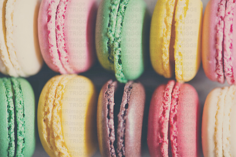 close up photograph of a selection of sweet french macarons, every color of the rainbow