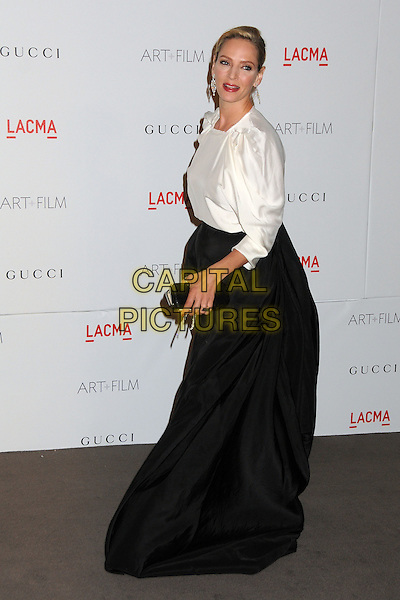 Uma Thurman.The Inaugural Art and Film Gala held at LACMA in Los Angeles, California, USA..November 5th, 2011.full length black skirt clutch bag white side.CAP/ADM/BP.©Byron Purvis/AdMedia/Capital Pictures.