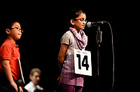 Olson Elementary's Anvika Annyapu spells a word, as Huegel Elementary's Gang Wang, Jr. waits in line, during the 2016 Madison All-City Spelling Bee at Madison Area Technical College's Mitby Theater