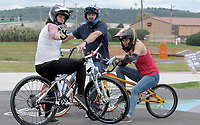 NWA Democrat-Gazette/DAVID GOTTSCHALK Romana Labounkova (from left), of the Czech Republic, Jason Lind, of Springdale, and Vanessa Kager, of Austria, visit Tuesday, October 9, 2018, before taking a run on the pump track at the Runway Bicycle Skills Park at the Jones Center in Springdale. The park will host the Pump Track (bicycling) World Championships sponsored by Red Bull on Saturday, October 13. A pump track is designed so that bikers pump and push on hills and turns to build speed using their upper body and hips instead of pedaling.