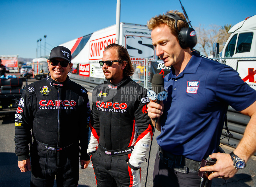 Feb 25, 2018; Chandler, AZ, USA; NHRA top fuel driver Steve Torrence (center) and father Billy Torrence (left) talks with Fox Sports 1 television announcer Bruno Massel during the Arizona Nationals at Wild Horse Pass Motorsports Park. Mandatory Credit: Mark J. Rebilas-USA TODAY Sports