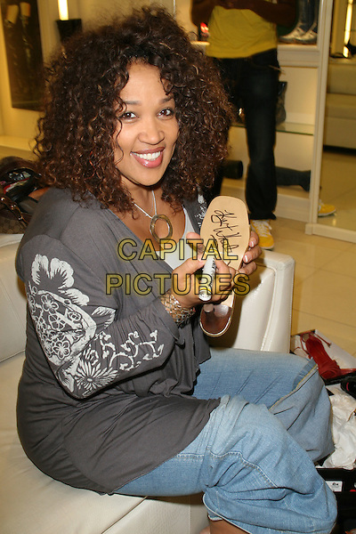 "KIM WHITLEY .Carmen Steffens Launches Month-Long ""These Boots were Made For Walking"" Campaign For Charity held at the Westfield Fashion Square, Sherman Oaks, California, USA, 09 October 2008..half length sitting signing autographing shoes jeans grey gray top .CAP/ADM/KB.©Kevan Brooks/Admedia/Capital PIctures"