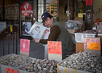A vendor reading a Chinese newspaper is seen behind stalls in Toronto Chinatown April 23, 2010. Toronto Chinatown is an ethnic enclave in Downtown Toronto with a high concentration of ethnic Chinese residents and businesses extending along Dundas Street West and Spadina Avenue.