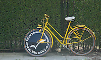 A yellow bicycle advertising www.bluesky.eu parked in Parc du Cinquantenaire (Jubilee Park) in Brussels, Belgium