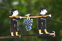 A wrought iron painted sign that illustrates the theme of champagne and wine production: two men in black holding a pole on the shoulders from which (in a religious reference) a giant bunch of grapes hang, the village of Hautvillers in Vallee de la Marne, Champagne, Marne, Ardennes, France
