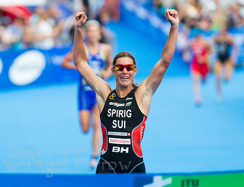 23 JUN 2012 - KITZBUEHEL, AUT - Nicola Spirig (SUI) of Switzerland (centre in black and red) celebrates winning the elite women's 2012 World Triathlon Series round in Schwarzsee, Kitzbuehel, Austria as she runs to the finish line followed by Lisa Norden (SWE) of Sweden (left, in blue and yellow) and Barbara Riveros Diaz (CHI) of Chile (second from right in red) and Andrea Hewitt (NZL) of New Zealand (on right in dark grey) (PHOTO (C) 2012 NIGEL FARROW)