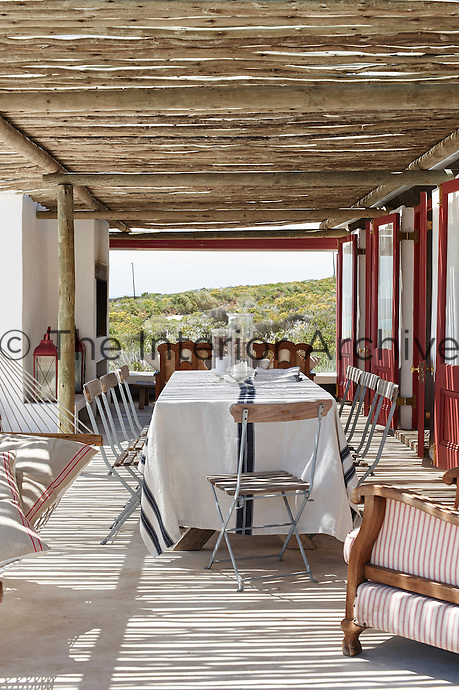 A table and chairs on a covered terrace in the sunshine.