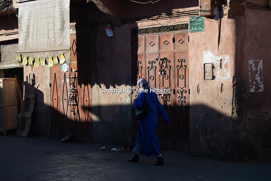 Women in blue Djellabah, walking down Rue Bab Ksiba, Kasbah, Medina, Marrakech, Morocco.