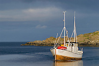 Wooden fishing boat returns to harbor in the village of Stamsund, Lofoten islands, Norway