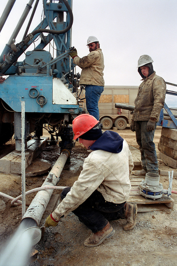 Drillers check the discharge from a fresh well for metal and plastic fragments outside of Sheridan, Wyoming where a rush is on for the extraction of coal bed methane gas. The natural gas is released by coal seams below the ground when water is removed from the coal. Local ranchers and environmentalists are concerned that well water levels will drop as a result from all the water removal by drilling companies, or that hazardous pollutants will sterilize the ground where the water is dumped. Erosion, pollution of fisheries and increased flooding are other concerns.