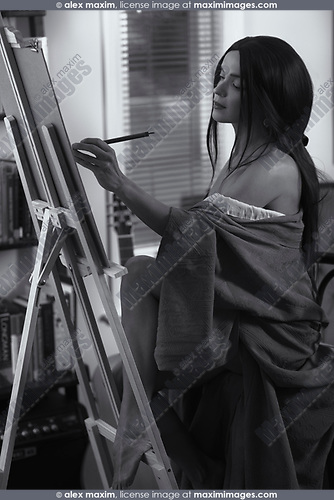Artistic sensual portrait of a beautiful young woman fine artist painting in her home studio on an easel Black and white
