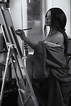 Artistic sensual portrait of a beautiful young woman fine artist painting in her home studio on an easel Black and white Image © MaximImages, License at https://www.maximimages.com