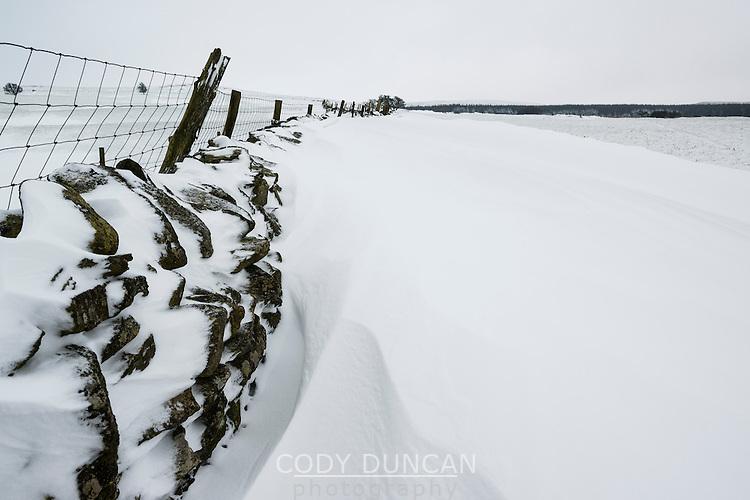 Snowdrift builds against stone wall, near Llandrillo, Denbighshire, Wales