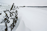Snowdrift builds against stone wall, near Llandrillo, Denbighshire, Wales