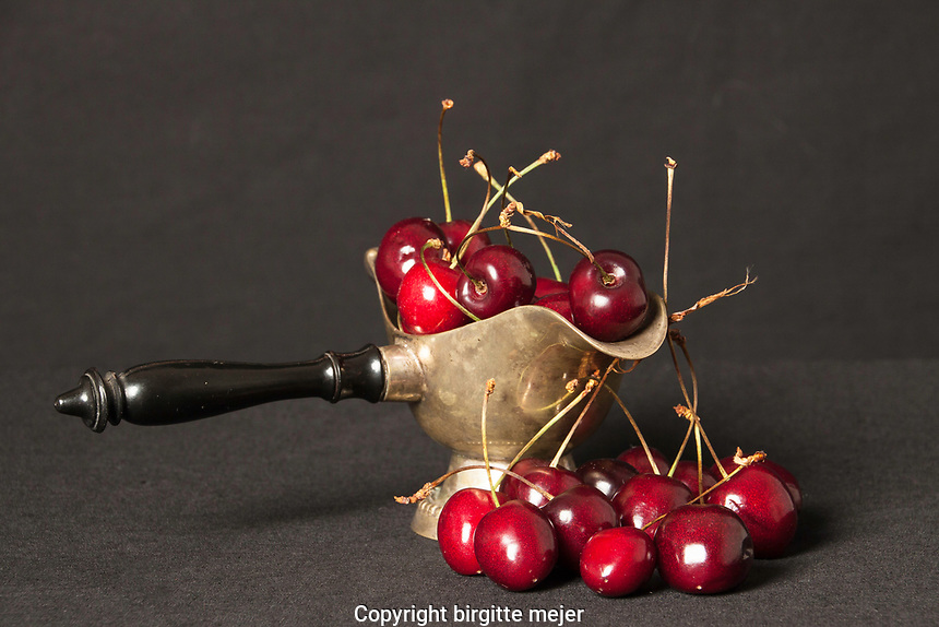 Cherries placed in an old silver saucer all placed on black backdrop