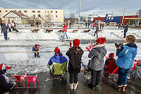 Race fans wave to Travis Beals as he runs down 4th avenue during the Ceremonial Start of the 2016 Iditarod in Anchorage, Alaska.  March 05, 2016